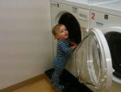 маленький мальчик стоит возле стиральной машины