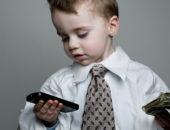 Мальчик в галстуке с телефоном и деньгами