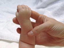 Детская ручка держит палец взрослой руки