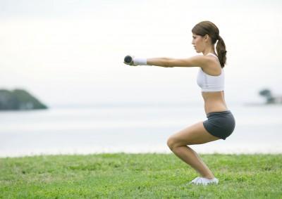 Девушка тренируется с гантелями