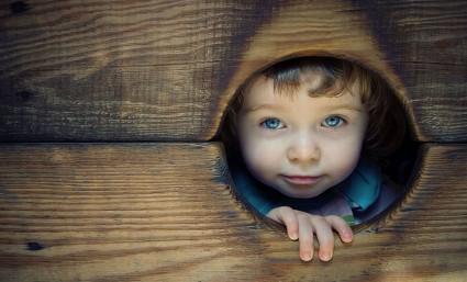 Ребёнок выглядывает из отверстия в дереве