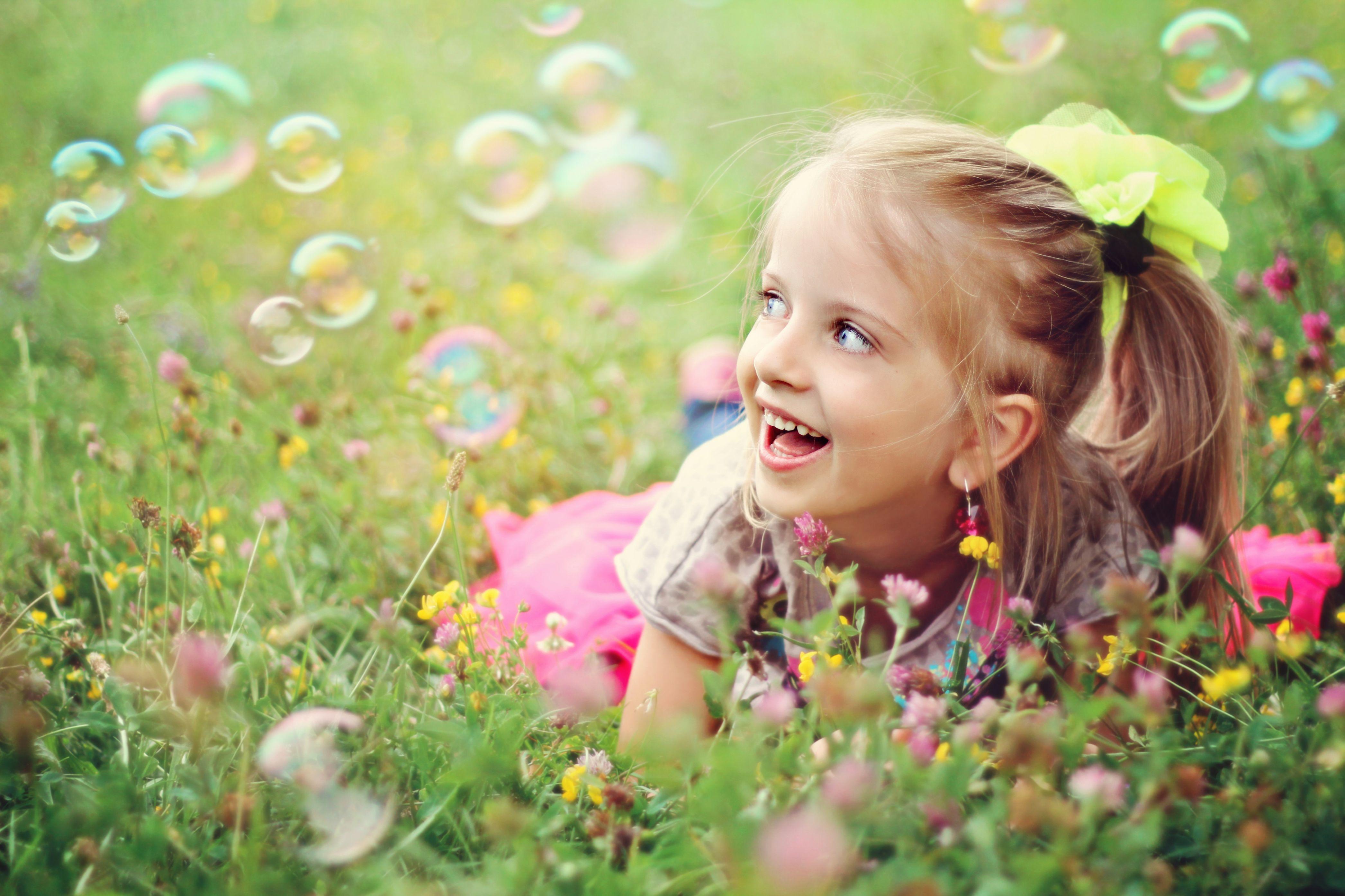Девочка на лугу с мыльными пузырями
