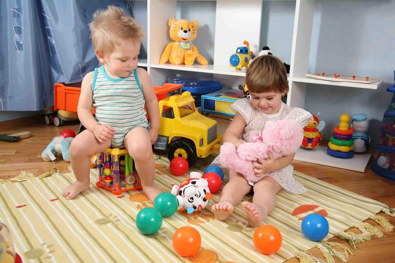 Мальчик и девочка сидят в комнате с игрушками