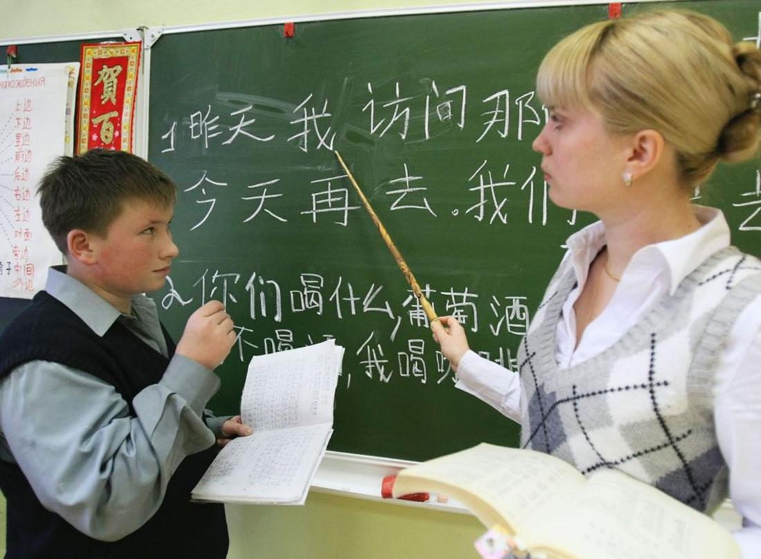 Учитель показывает на доске иероглифы ученику