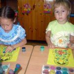 2 девочки разрисовывают матрёшку ватными палочками