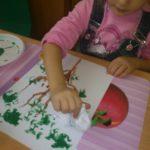Девочка рисует скомканной бумагой деревья