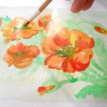 Рисуют оранжевые цветы по мокрому