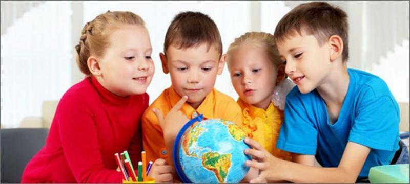 2 девочки и 2 мальчика рассматривают небольшой глобус, рядом стакан с фломастерами