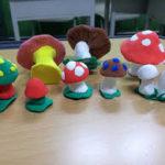 Разноцветные грибочки на зелёных кусочках пластилина-полянах