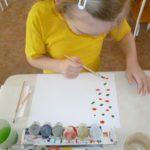 Ребенок наносит изображение на одну половину листа бумаги