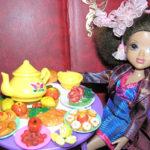 кукла за столом с угощением